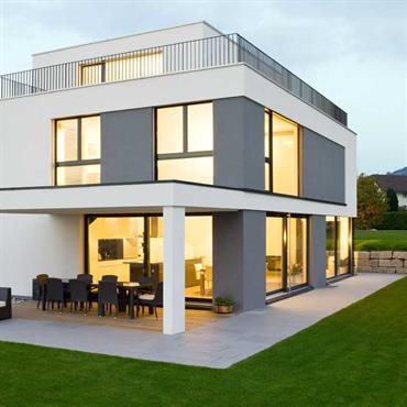 Maison contemporaine grise et blanche, entourée d'une pelouse.