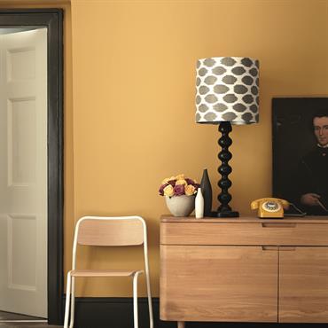 Entrée jaune paille avec meuble en bois clair, lampe à poser