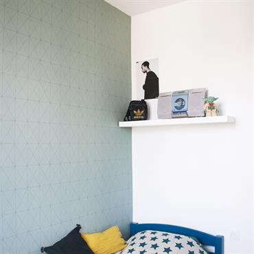 Pose de papier peint sur un des murs de la chambre
