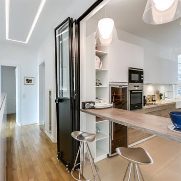 L'intégration de la cuisine contemporaine avec le reste de l'appartement haussmannien mise sur la modularité des espaces. Lorsque les propriétaires reçoivent de manière plus informelle, la verrière en acier est ...