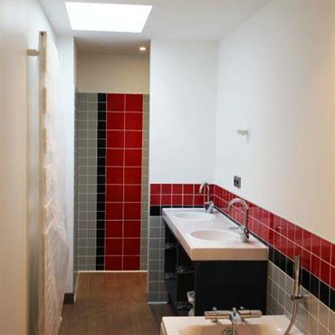 Salle de bain contemporaine avec baignoire. Carrelages rouges, gris et noirs. Parquet, murs blancs