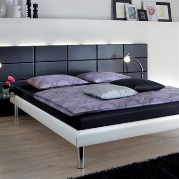 Chambre avec une tête de lit en cuir noir. Les murs de la chambre sont blancs