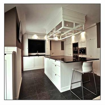 Cuisine moderne avec ilot central. Mobilier en bois peint en blanc, plan de travail laqué noir