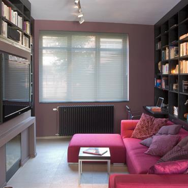 Salon TV et bibliothèque en bois foncé.