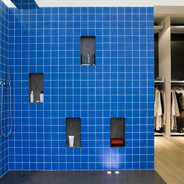 Douche italienne avec carrelage en verre teinté à l'acide bleu royal en guise de revêtement.