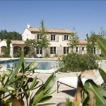 Cette maison provençale aux tons clairs offre un bel espace piscine dans un grand jardin paysagé.