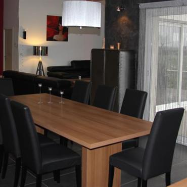 Salle à manger avec carrelage sombre, chaises noires et table en bois de couleur naturelle
