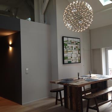 Salle à manger en double-hauteur en contraste avec le couloir plus intimiste