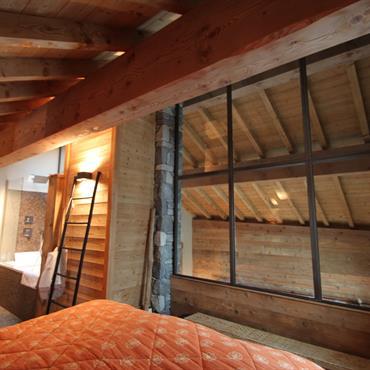 Chambre adultes avec salle de bain attenante. Sous les combles en mezzanine, baies vitrées donnant sur la pièce à vivre