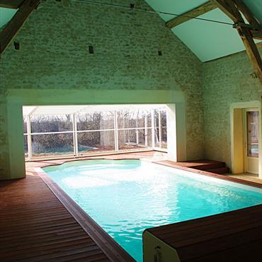 La piscine de 4×11 m chauffée à 28° toute l'année (géothermie) se trouve dans l'étable à la poutraison en chêne