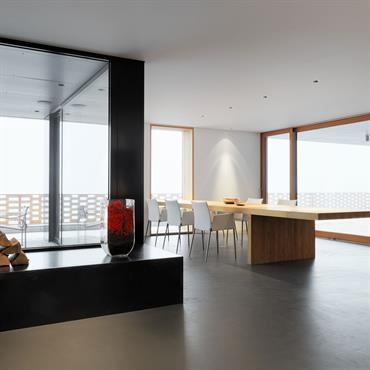 Salle à manger baignée de lumière naturelle. Grande table en bois massif, sol en béton ciré.