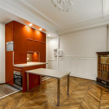 Cuisine d'appartement haussmannien avec rangements orange