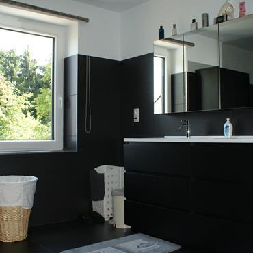 Salle de bain avec meubles et murs noirs. Plafond et haut du mur blancs