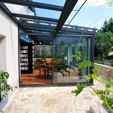 L'espace terrasse est optimisé avec une partie découverte pour profiter de l'extérieur et une partie habillée d'une véranda pour un agrandissement lumineux.