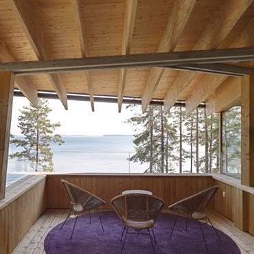 Terrasse nichée sous l'auvent, le garde coprs en verre permt une large vue sur le lac Saimaa