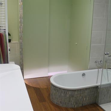 La salle de bain de plein pied dispose d'une douche à l'italienne avec des parois en verre sur mesure allant du sol au plafond.  La baignoire en acier bénéficie elle d'un ...