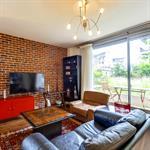 Salon avec mur en fausses briques et accès au jardin