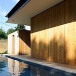 La piscine s'étire en rectangle le long de la façade en lames