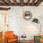 Salon avec poutres et murs anciens apparents
