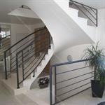 Escalier tournant traditionnel avec rambarde en fer