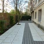 Terrasse en bois composite gris encastrées dans un dallage clair
