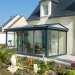 Véranda classique avec un toit en polycarbonate et baies vitées