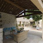 Terrasse couverte au charme provençal avec toiture à la charpente traditionnelle apparente