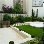 Petit jardin clos de murs avec terrasse et partie engazonnée