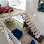 L'escalier suspendu en chêne blanchi qui monte à la mezzanine