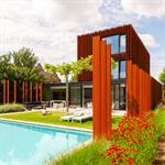 Maison en acier Corten ouvrant sur un jardin avec piscine