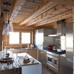 La cuisine contemporaine s'intègre à merveille dans l'environnement chalet à la charpente