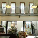 Salle de vie double hauteur donnant sur la serre bioclimatique