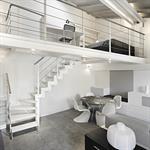 Pièce à vivre avec escalier menant à une mezzanine