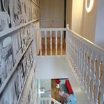 Le papier peint en imprimé gris habille la cage d'escalier