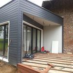 Les matériaux utilisés en façade sont le bois gris foncé en parement