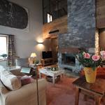 Salon de chalet de montagne chaleureux avec cheminée en pierres