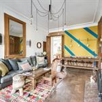 Salon familial avec parquet et mur coloré